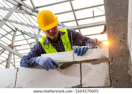 bricklayer builder working with autoclaved aerated concrete blocks. Walling, installing bricks on construction site, Engineering and constructions concepts. #1664570605