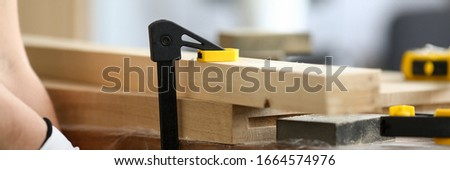 Woodworker fastens wooden parts on workbench. Vise is installed on workbench. Careful processing and finishing wooden products using special carpentry tools. Resizing shape and appearance wood