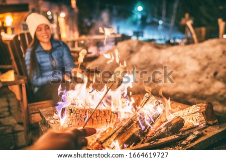 Winter holiday ski resort woman roasting marshmallows in BBQ firepit afterski fun leisure activity with friends. Couple grilling marshmallow stick in fire. #1664619727