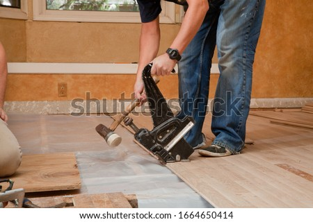 Worker uses Pneumatic Hardwood Nailer on a new floor installation. Royalty-Free Stock Photo #1664650414