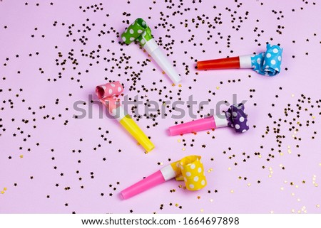 Birthday or party colorful happiness background with party noise whistles and confetti on pink background. Carnival air blowers flat lay, top view image.
