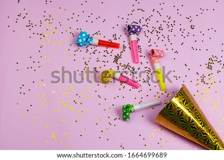 Birthday or party colorful happiness background with party noise whistles, birthday hat and confetti on pink background. Carnival air blowers flat lay, top view image.