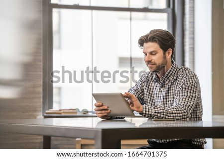 Office life. A man working on a digital tablet at an office desk. #1664701375