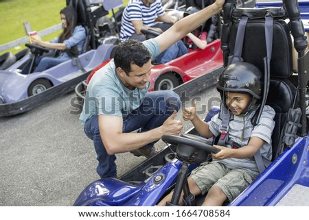 Boys and men go-karting on a track. #1664708584