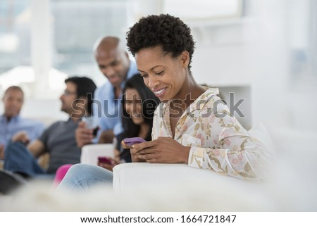 A group of people gathering together for a party or an office event. A woman checking her smart phone. Royalty-Free Stock Photo #1664721847