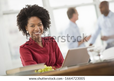 A business environment, a light and airy workplace in the city. A woman seated at a desk using a laptop computer. Royalty-Free Stock Photo #1664723005