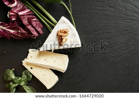 Delicious brie cheese on black background. Brie type of cheese. Camembert. Fresh Brie cheese and a slice on stone board. Italian, French cheese. #1664729020