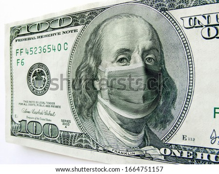 This photo illustration of Ben Franklin wearing a healthcare surgical mask on a one hundred dollar bill illustrates the many problems of the   Coronavirus, including medical, travel  and economic.  #1664751157