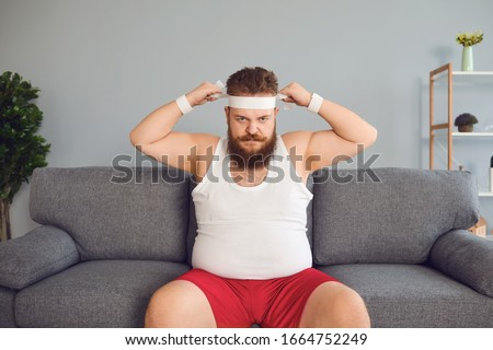 Funny fat man in sportswear is sitting on the sofa in the room #1664752249
