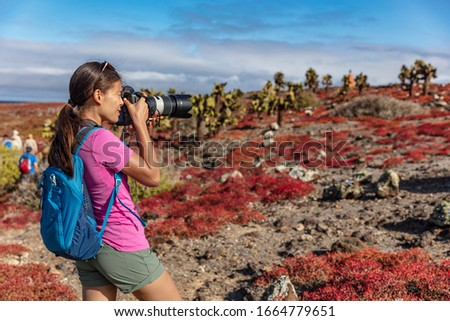 Galapagos tourist taking pictures of wildlife, landscapes and animals on North Seymour, Galapagos Islands. Amazing animals and wildlife during Galapagos cruise ship vacation travel