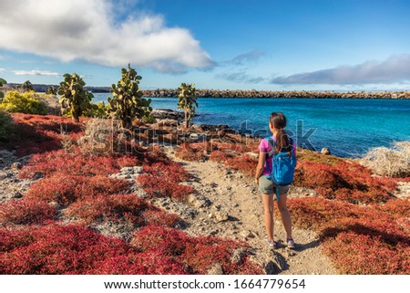 Galapagos tourist on adventure hiking enjoying landscape and animals on North Seymour, Galapagos Islands. Amazing animals and wildlife during Galapagos cruise ship vacation travel