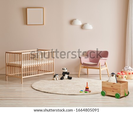 Wooden crib and bed for baby room, pink chair, carpet and frame on the wall. Royalty-Free Stock Photo #1664805091
