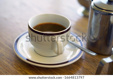 High angle view of a full coffee cup on table #1664813797