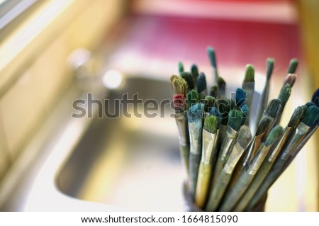 View of paint brushes in a cup against blurred background #1664815090