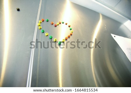 View of magnets in the shape of a heart on refrigerator #1664815534