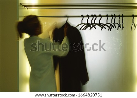 Blurred view of a woman hanging up her coat in a closet #1664820751