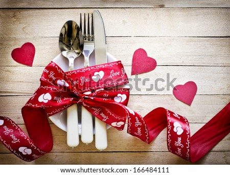 Valentines day table setting with plate, knife, fork, red ribbon and hearts/ Holidays background/ Valentines day background #166484111