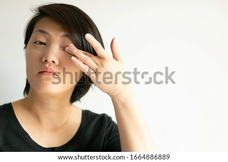 Portrait of an Asian woman that itch her eye and rub it with a finger; that one of forbiddance for the contagious disease situation. concept of healthcare and medical. Royalty-Free Stock Photo #1664886889