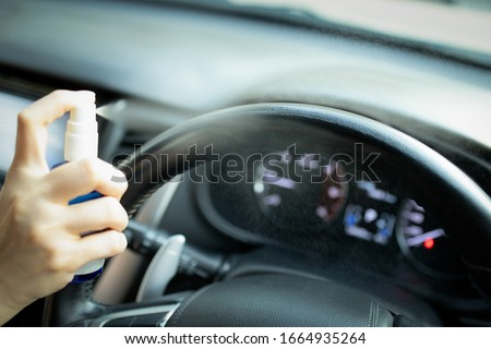 Hand of woman is spraying alcohol,disinfectant spray on steering wheel in her car,prevent infection of Covid-19 virus,contamination of germs or bacteria,wipe clean surfaces that are frequently touched #1664935264