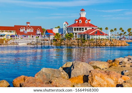 Shoreline Village sits in Rainbow Harbor In Long Beach, California. Shops line the edge of the marina area, and boats are docked in it's harbor. Royalty-Free Stock Photo #1664968300
