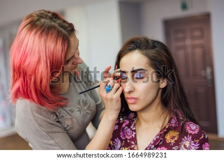 Make-up artist working in studio with young beautiful woman. #1664989231