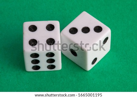 lucky seven - a pair of dice on a green background showing four and three #1665001195