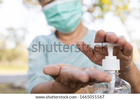 Asian elderly people wearing protective mask,using alcohol antiseptic gel,prevent infection,outbreak of Covid-19,senior woman washing hand with hand sanitizer to avoid contaminating with Coronavirus   #1665055567