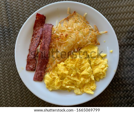 Picture of a traditional American style breakfast. Eggs, turkey bacon and potatoes.