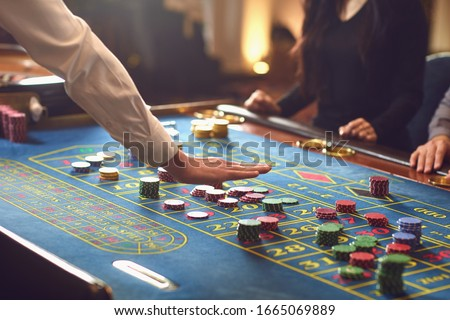 People gambling at roulette poker in a casino. #1665069889