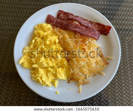 Scrambled eggs, turkey bacon and hashbrowns. Traditional American breakfast.