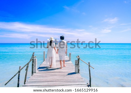 Couple in white summer clothing on a wooden pier extending to the sea beach. Happy summer vacation #1665129916