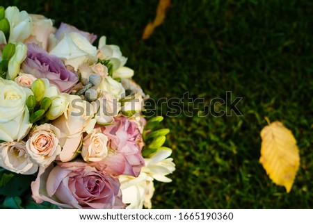 Picture of a wedding bouquet , Wedding bouquet of pink and white roses, white and yellow flowers with green, decorated with silk ribbons, lie on the green grass. The bride's bouquet.