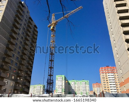 A tall house is built by a contractor with a crane. Photo of the house on a background of blue cloudless sky. Construction site for demounting the construction industry #1665198340