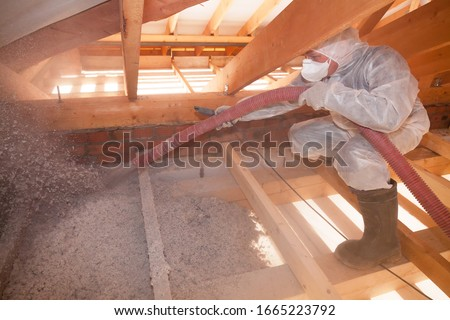 A man is spraying ecowool insulation in the attic of a house. Insulation of the attic or floor in the house #1665223792