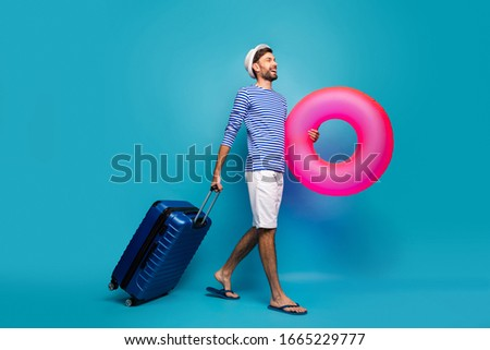 Full body profile photo of handsome guy traveler rolling case hold big pink lifebuoy want to see ocean wear striped sailor shirt cap shorts flip flops isolated blue color background #1665229777