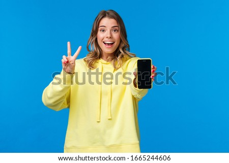 Optimistic cute blond european girl with short haircut, yellow hoodie, showing kawaii peace gesture and mobile phone display as using photo filter to edit and post pic online, blue background
