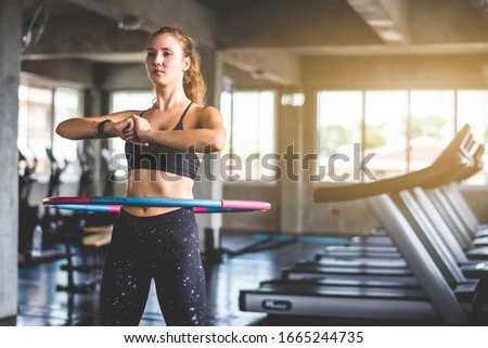 Beautiful young attractive Caucasian woman doing hula hoop during an exercise class at sport gym. Healthy sports lifestyle, Fitness, Healthy and workout concept. Royalty-Free Stock Photo #1665244735