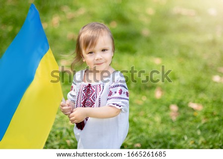 Child carries fluttering blue and yellow flag of Ukraine in field. Ukraine's Independence Day. Flag Day. Constitution day. Girl in traditional embroidery with flag of Ukraine #1665261685