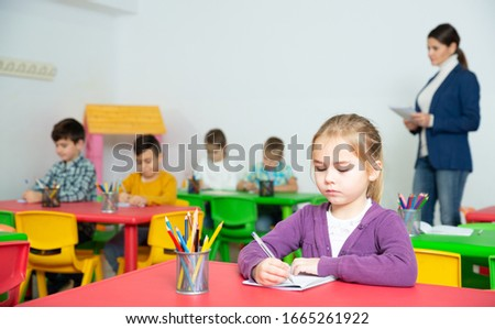 Portrait of little assiduous girl with pen and notebook at lesson in elementary school Royalty-Free Stock Photo #1665261922
