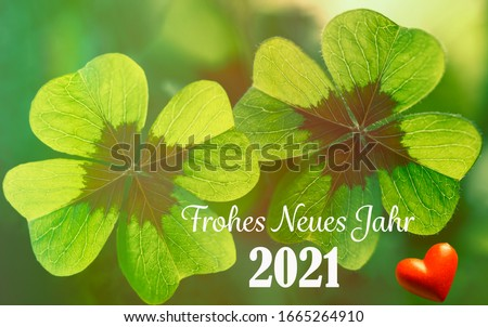 Decoration with four leaf clover and heart for New Year 2021 with text in german means in english HAPPY NEW YEAR 2021