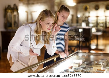 Young woman visitor with daughter looking to art objects under glass  with guide book in museum Royalty-Free Stock Photo #1665268570