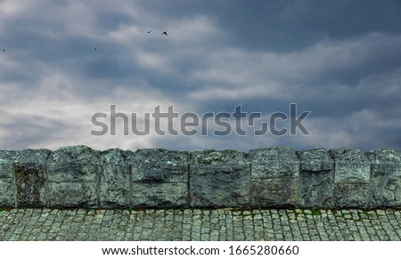 paved road stone fence foreground frame object on moody dramatic cloudy stormy sky background scenic view with flying birds wallpaper background space for copy or your text here