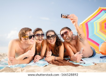 summer, holidays, vacation, technology and happiness concept - group of smiling people in sunglasses taking selfie with smartphone on beach