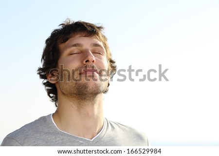 Attractive man breathing outdoor with the sky in the background              Royalty-Free Stock Photo #166529984