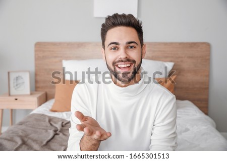 Young man video chatting at home Royalty-Free Stock Photo #1665301513