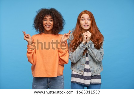 Studio photo of hoping attractive young women looking worringly at camera and keeping their hands raised, isolated over blue background in casual wear #1665311539