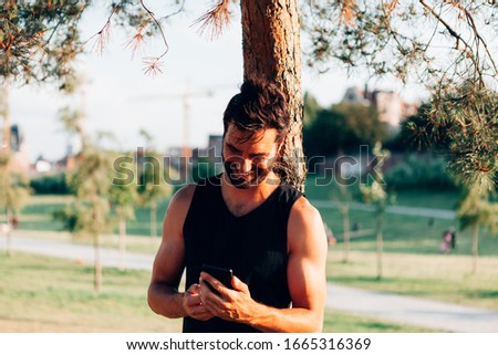 smiling attractive sporty man in tank top leaning against a tree looking at his mobile phone in workout break #1665316369