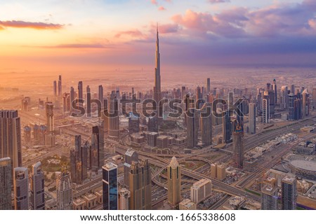 Aerial view of Burj Khalifa in Dubai Downtown skyline and highway, United Arab Emirates or UAE. Financial district and business area in smart urban city. Skyscraper and high-rise buildings at sunset. Royalty-Free Stock Photo #1665338608