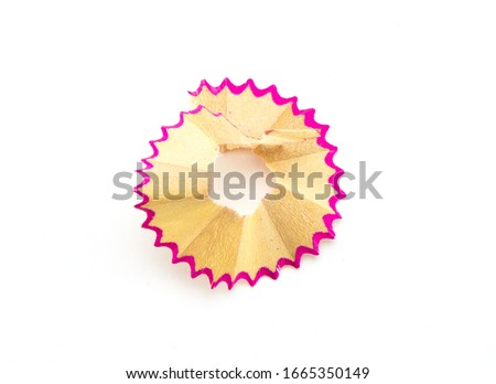 Round neat shavings from sharpening a wooden pencil with a pink border. White isolated background, close-up shot