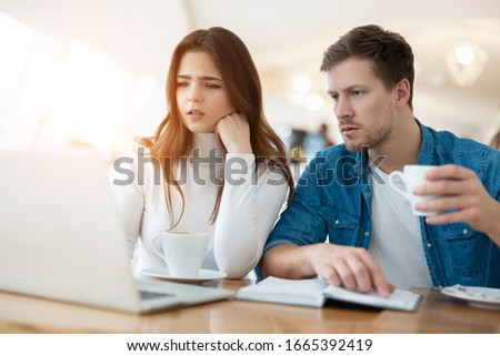 two young colleagues brunette woman and handsome man working in laptop during lunch break at cafe, looking serious, teamwork and multitasking concept #1665392419